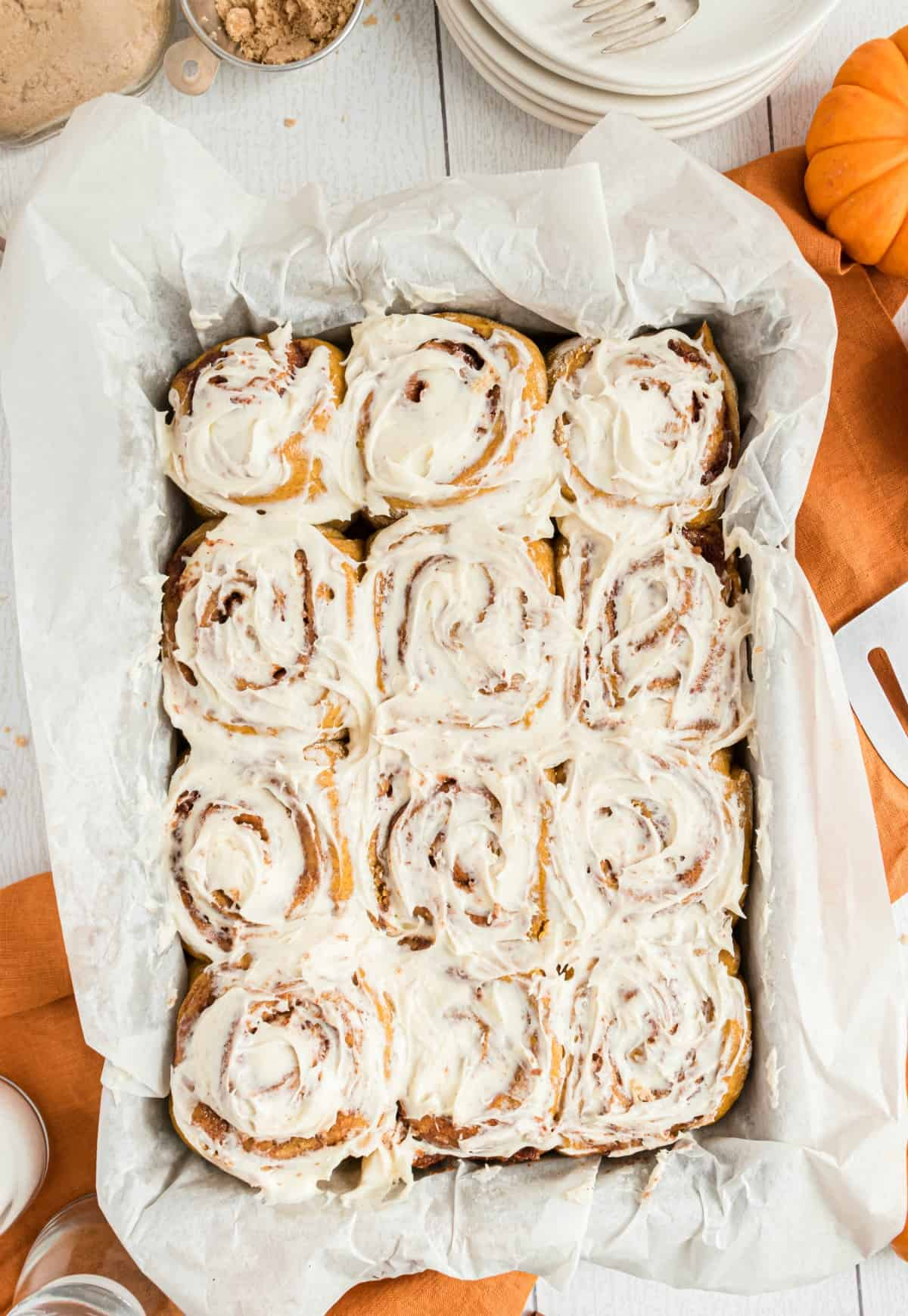 Pumpkin cinnamon rolls with maple icing in a parchment paper lined 13x9 baking dish.