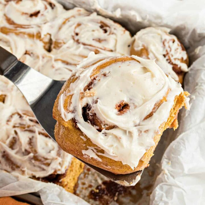 Pumpkin cinnamon roll being lifted out of the pan with a spatula.