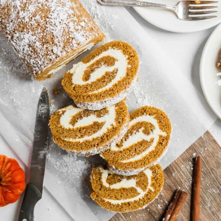 Sliced pumpkin roll with cream cheese frosting filling.