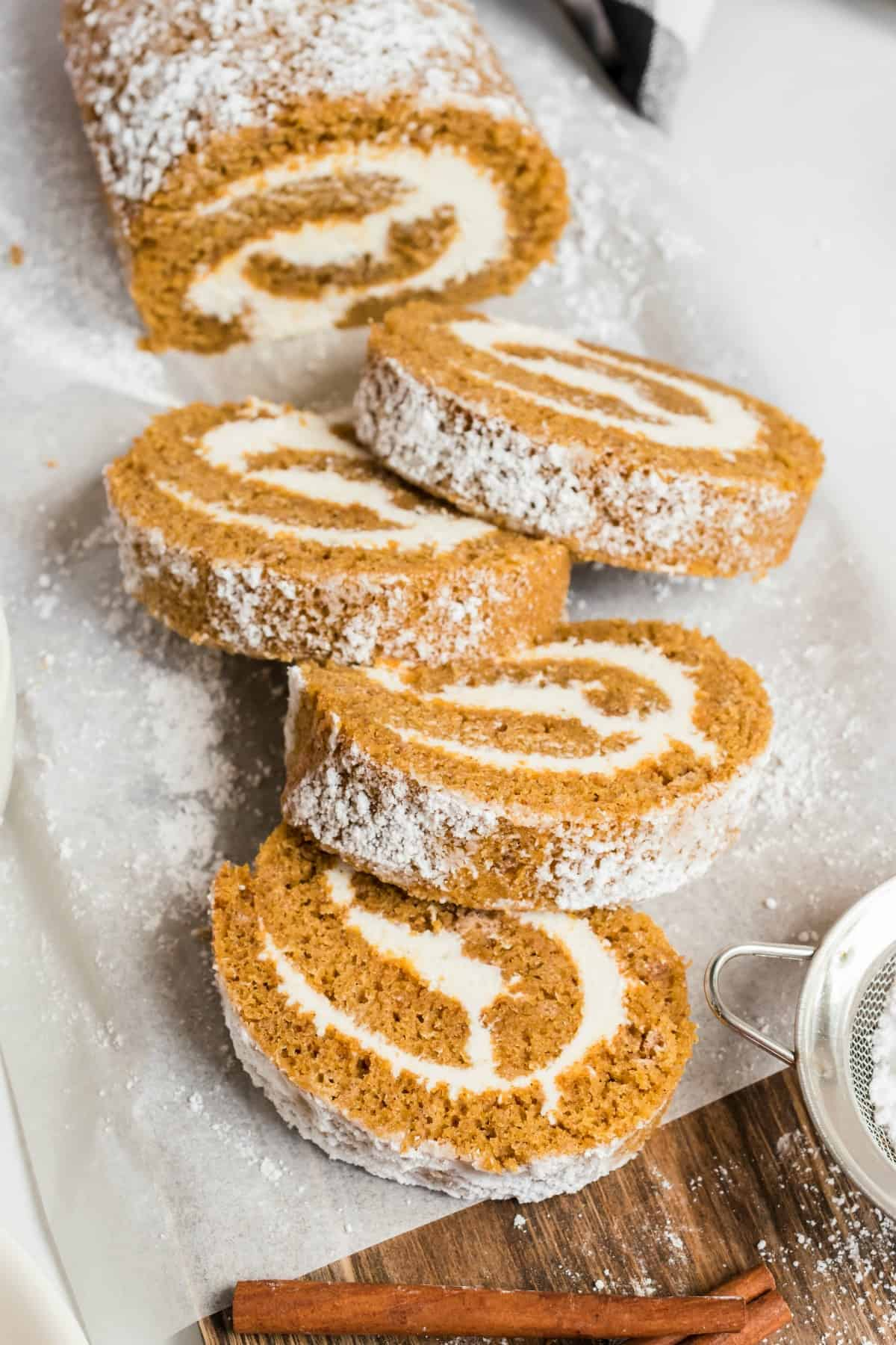 Pumpkin roll slices fanned out on parchment paper, with cream cheese frosting.