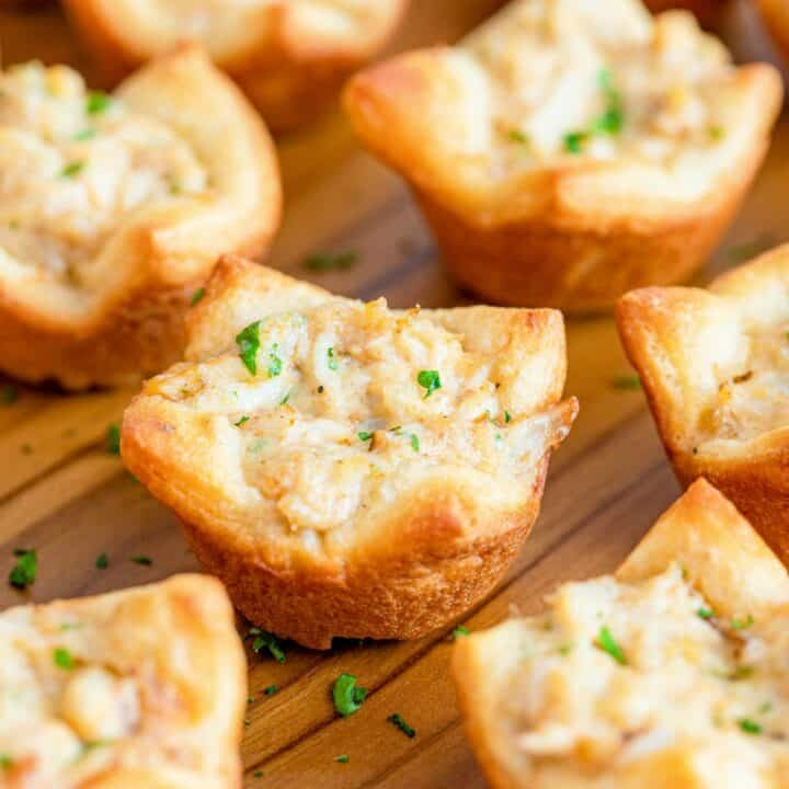 Baked crab puffs on a wooden tray.