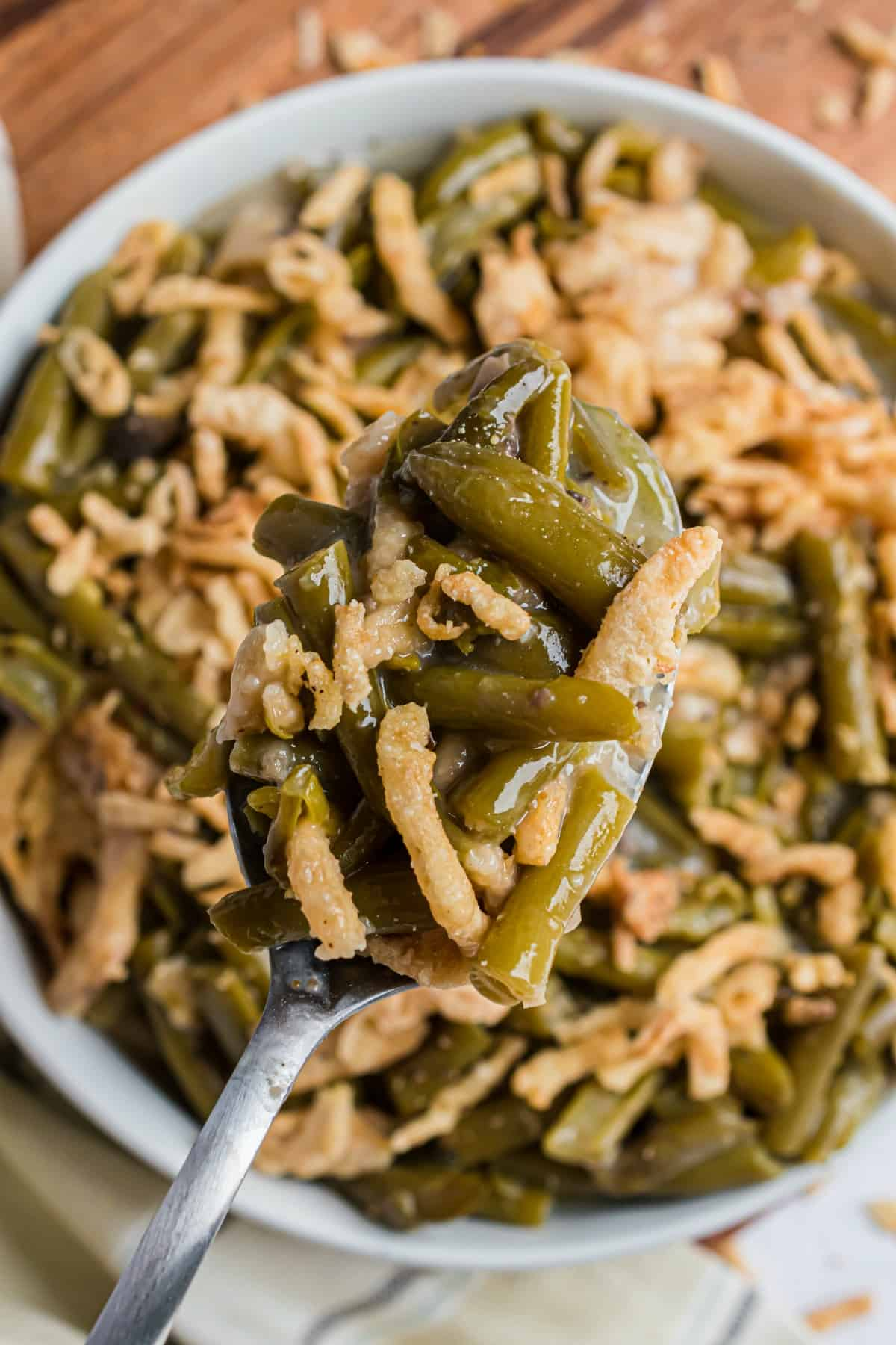 Serving dish with green bean casserole and french fried onions.