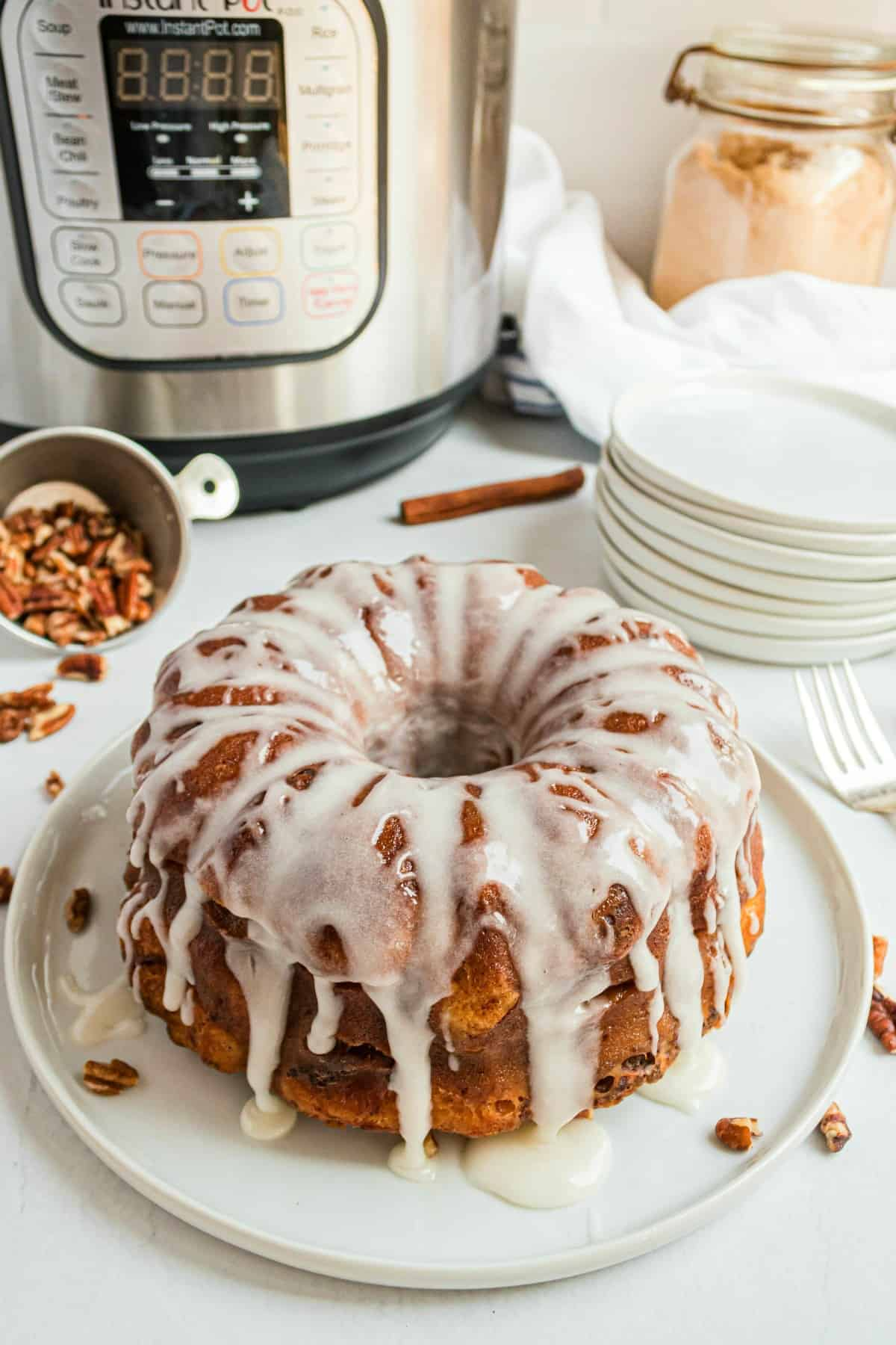 Cinnamon roll bread on a white serving plate with instant pot in background.