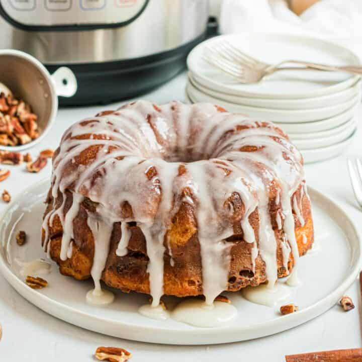 Loaf of cinnamon roll bread on a white serving plate and drizzled with icing.