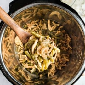 Instant pot green bean casserole being lifted by wooden spoon.