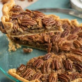 Pecan pie slice being lifted out of pie with spatula.
