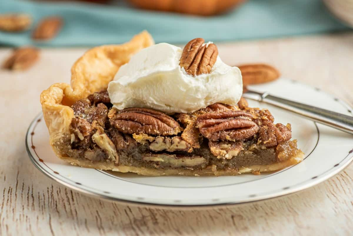 Slice of pecan pie with whipped cream on top.
