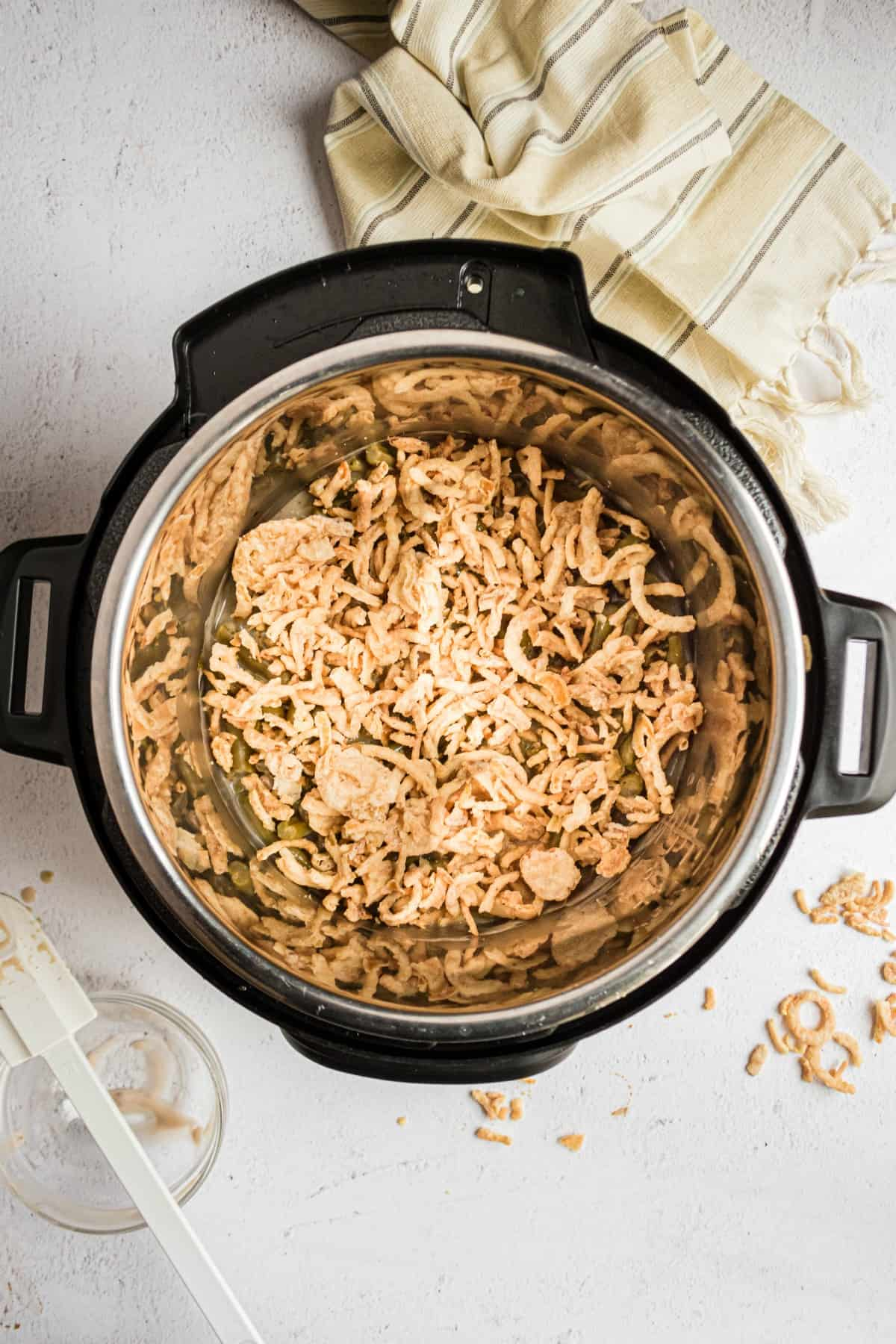 Green bean casserole in the pressure cooker topped with crispy fried onions.