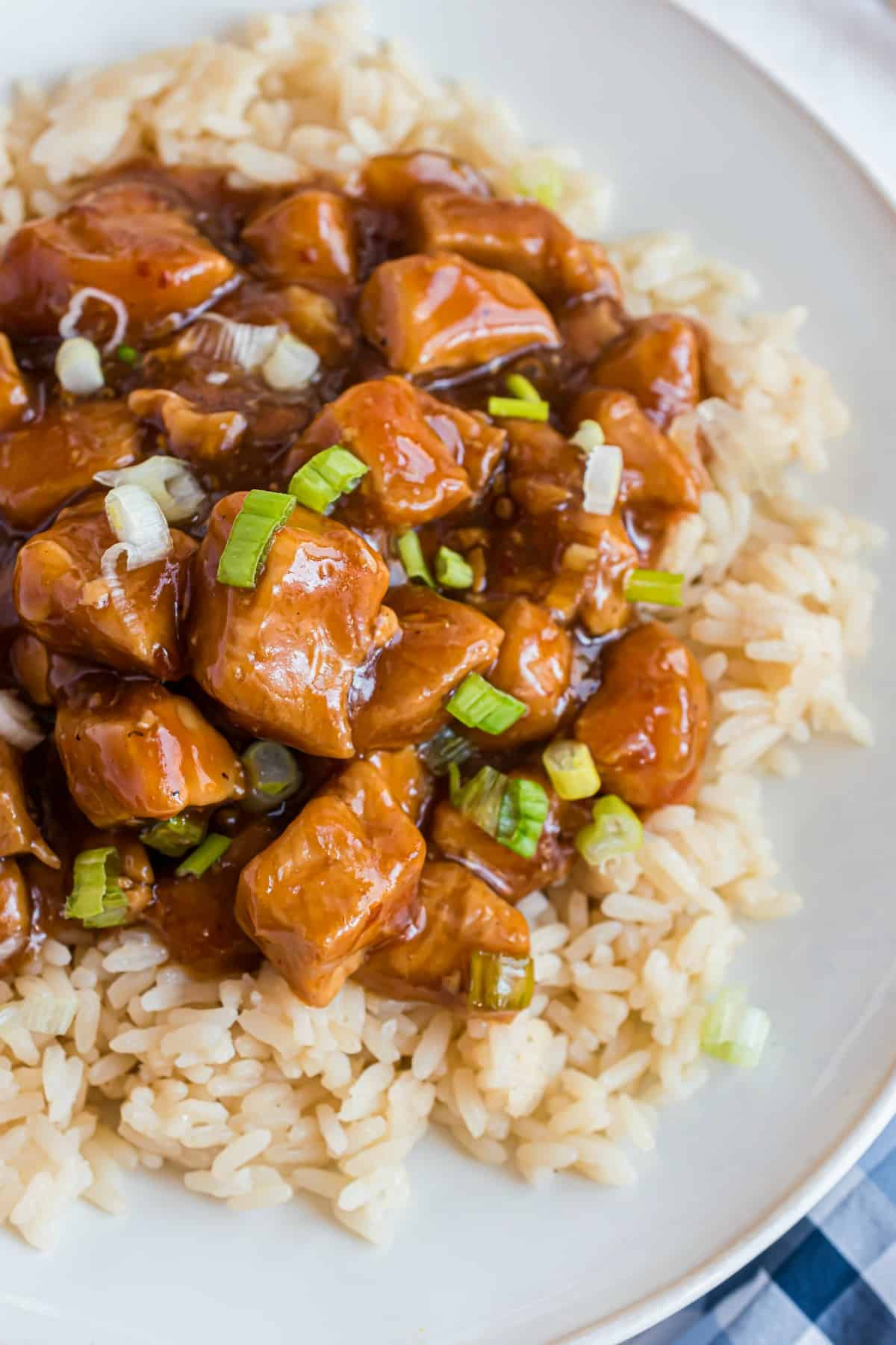 Brown rice with orange chicken on a white plate.