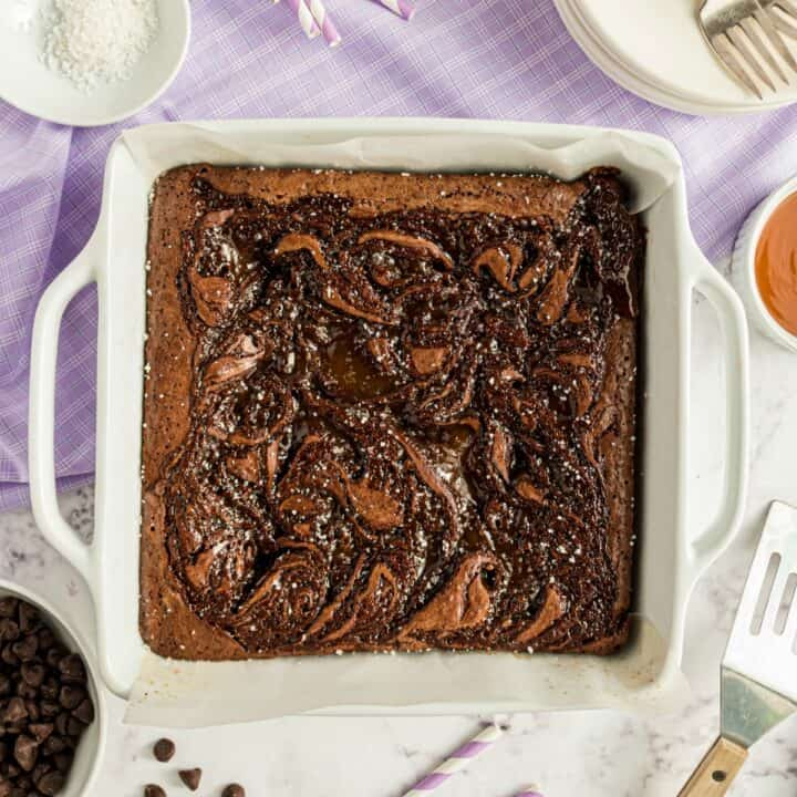Uncut brownies with caramel swirl in a white baking dish.