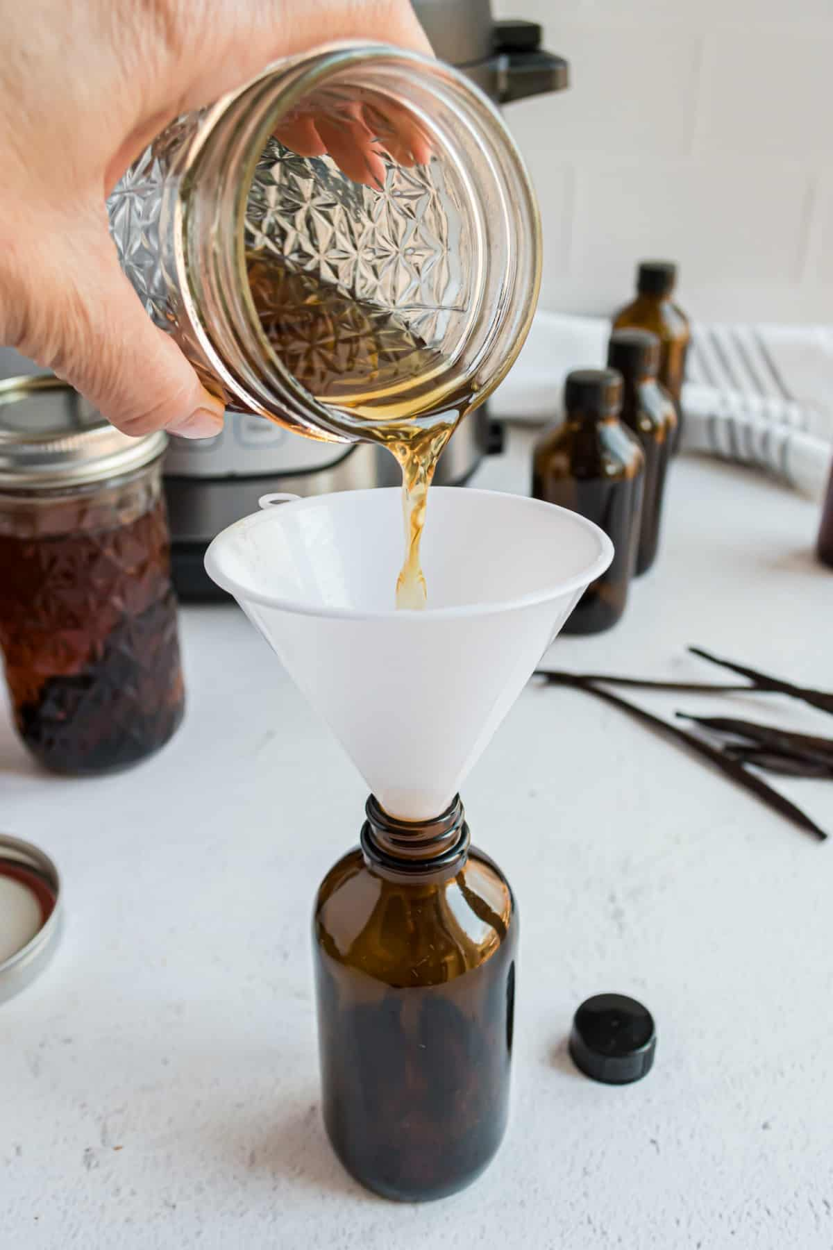 Pouring homemade vanilla extract into glass bottles.
