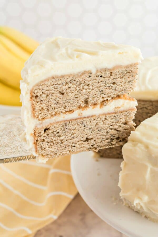 Slice of banana cake with cream cheese frosting.