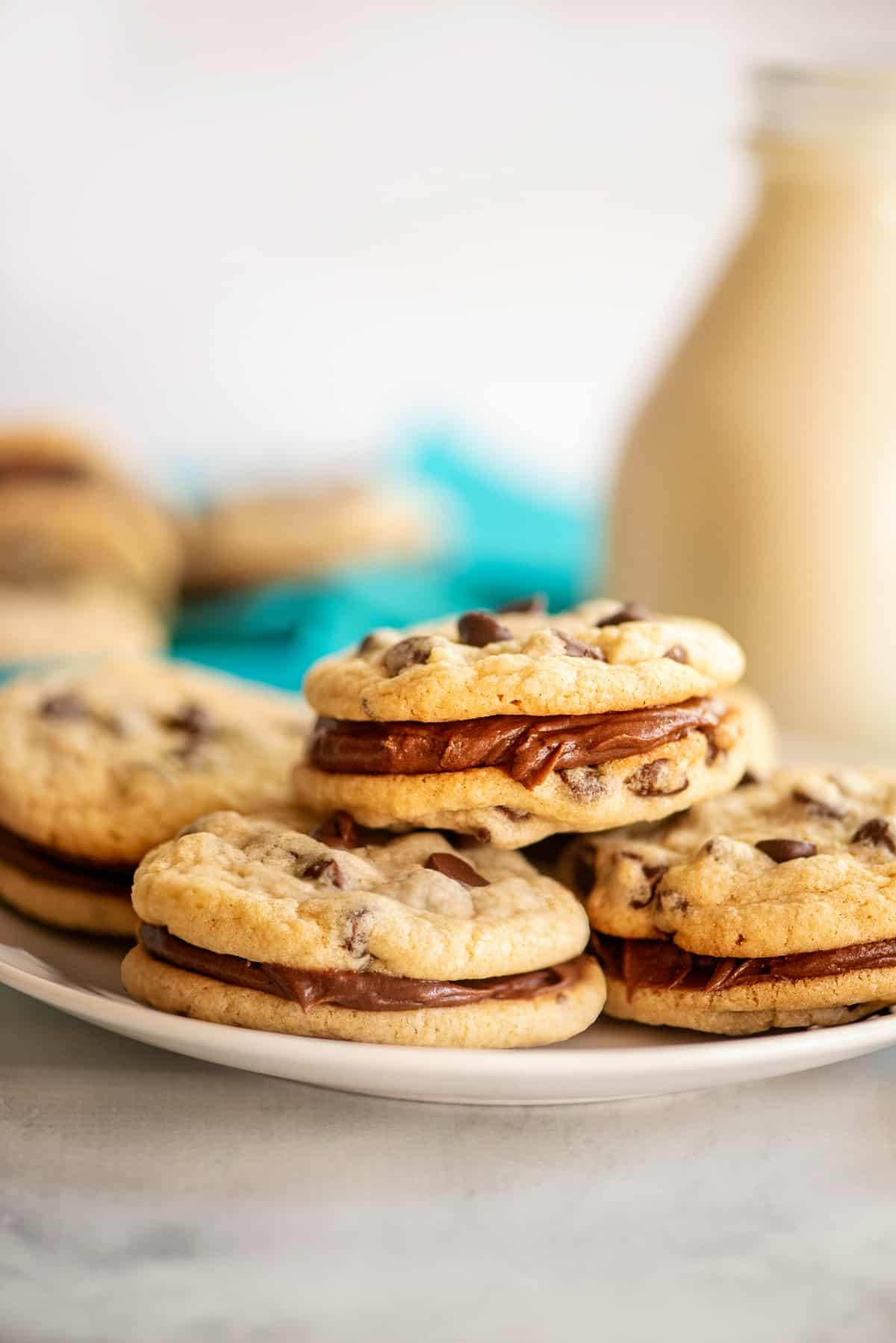 Chocolate Chip cookie sandwiches stacked on a white plate.