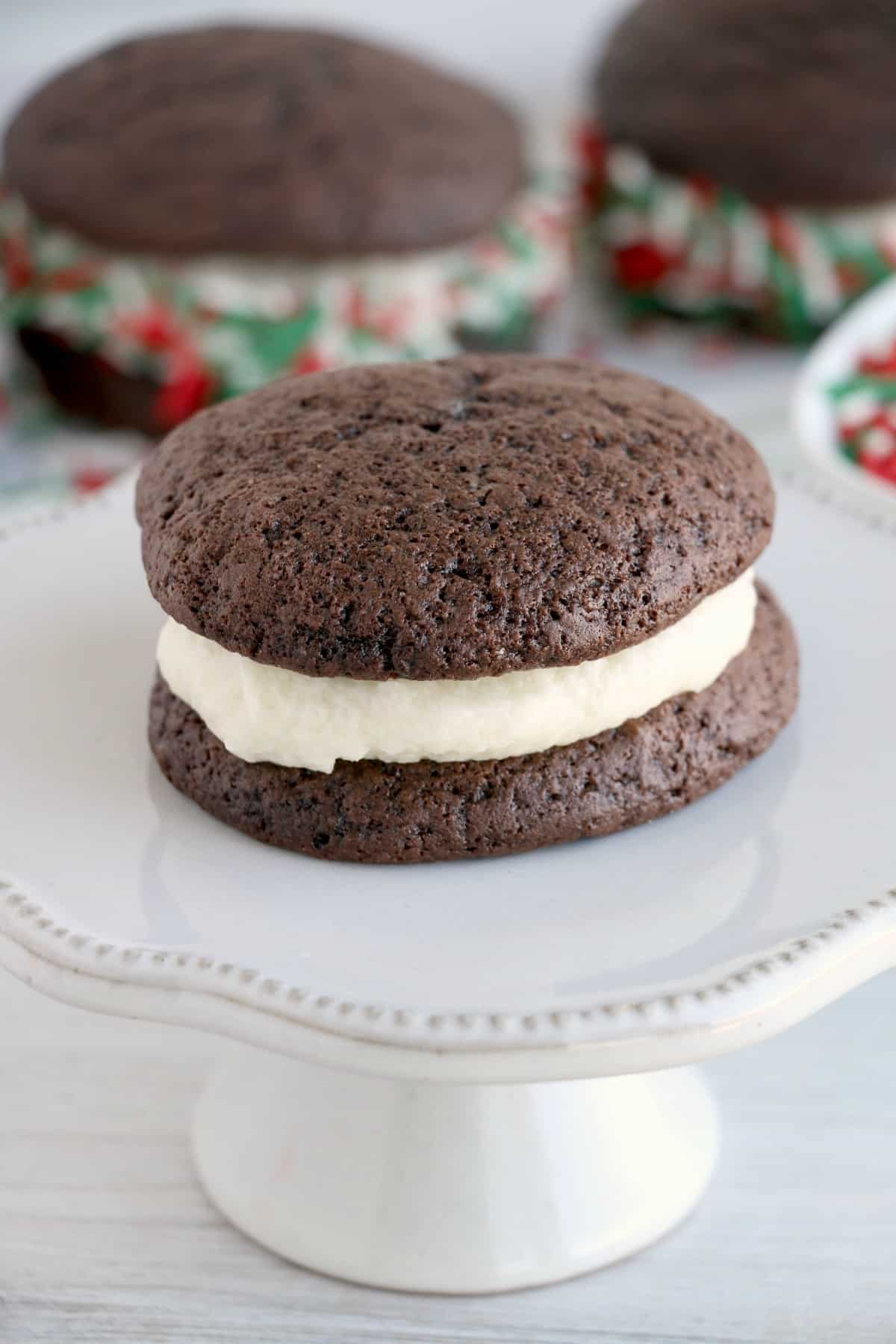 Chocolate whoopie pie with cream filling on small cake stand.