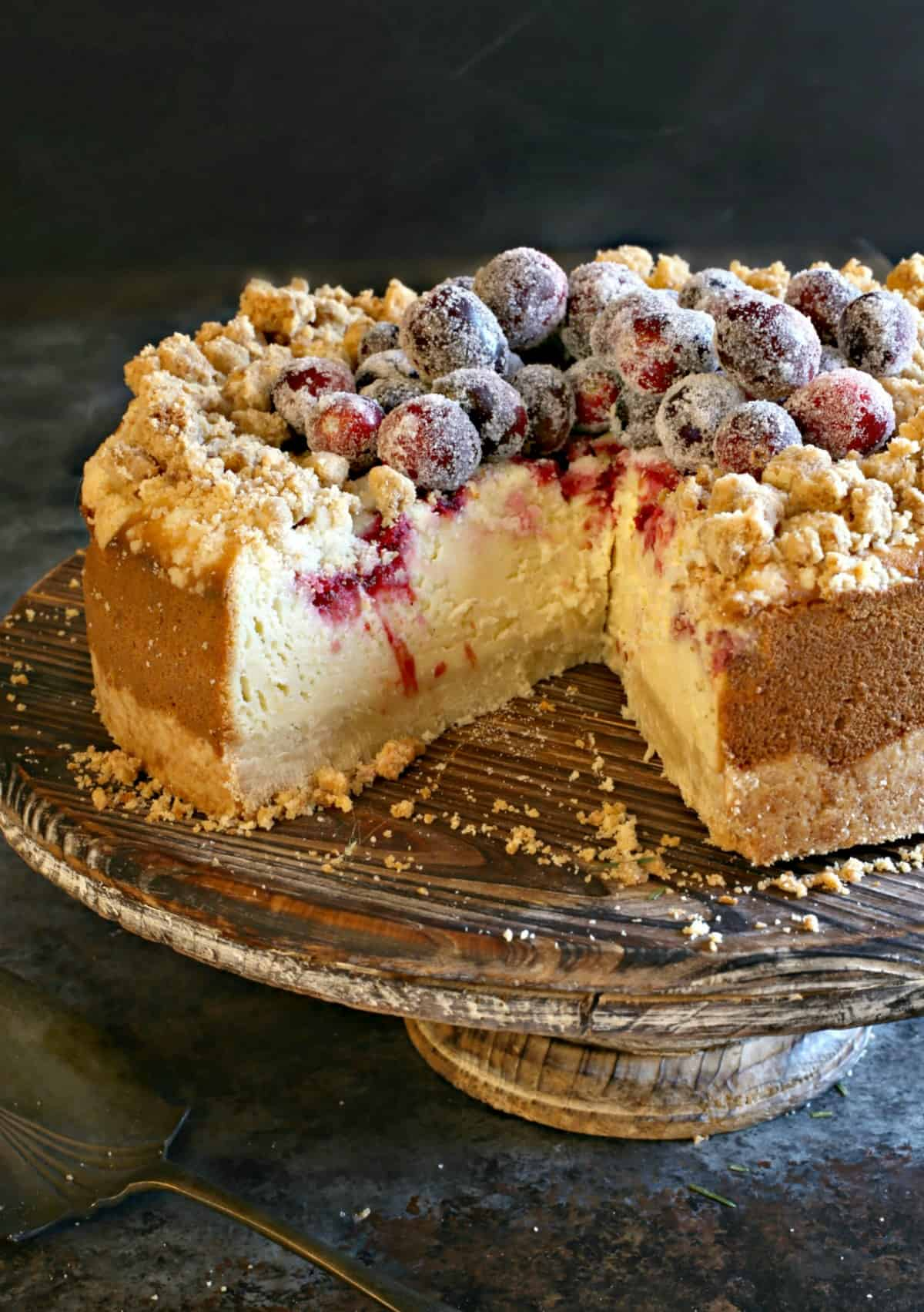 Cranberry cheesecake with slice removed and filling exposed.