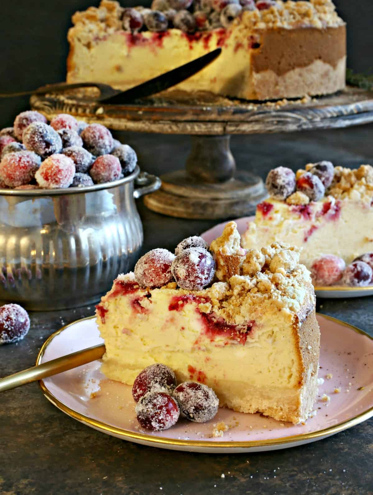Slice of cranberry cheesecake with sugared cranberries.