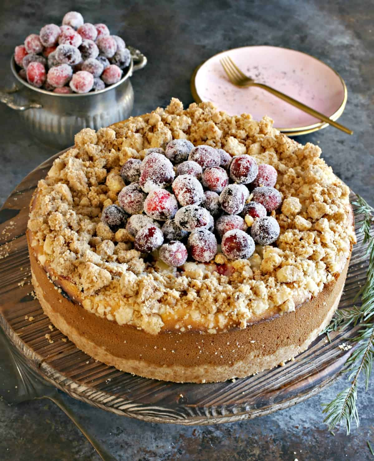 Cranberry cheesecake uncut on a wooden cake platter.