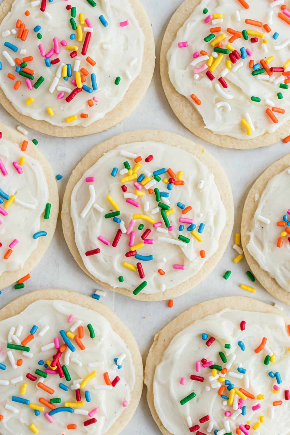 Sugar cookie frosting on circle cookies with festive sprinkles.