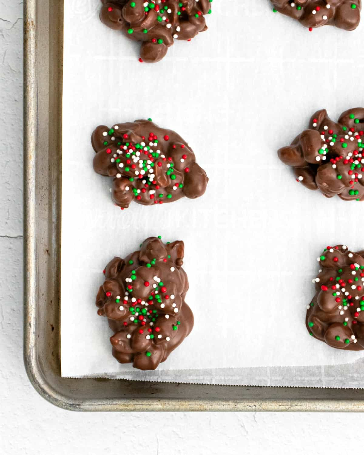 Three ingredient crock pot candy on parchment paper lined baking sheet.