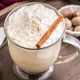 Eggnog with whipped cream and cinnamon stick in glass mug.