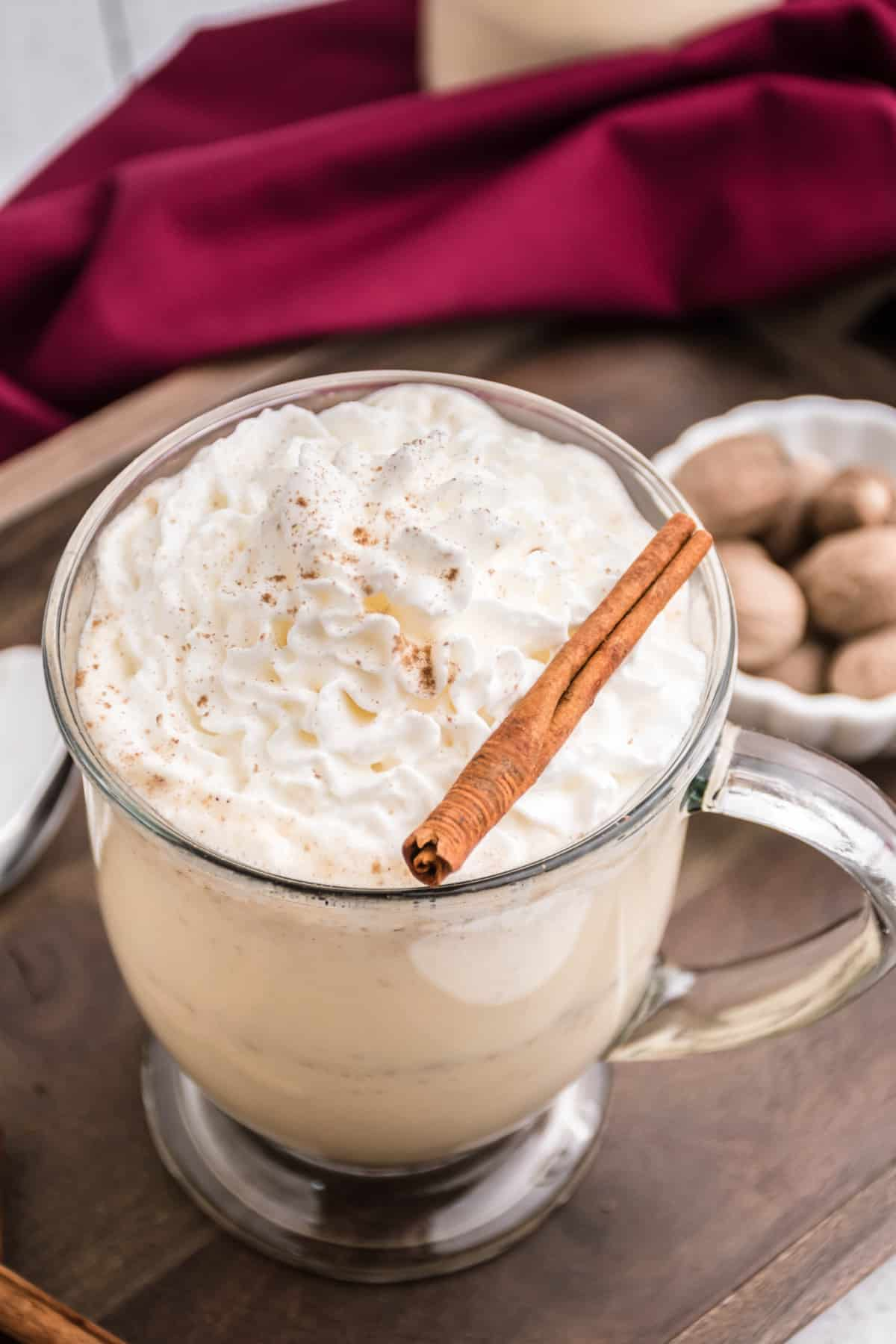 Clear glass mug with eggnog, whipped cream, and cinnamon stick.