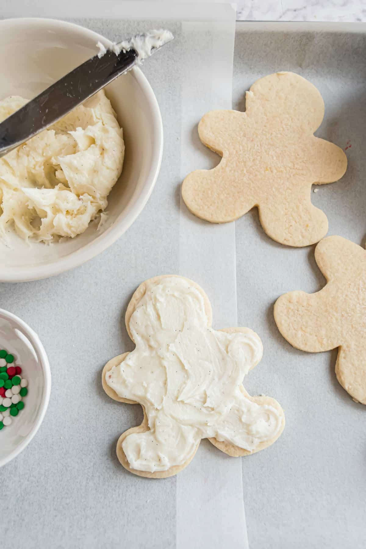 Sugar cookie frosting on gingerbread cut out cookie.