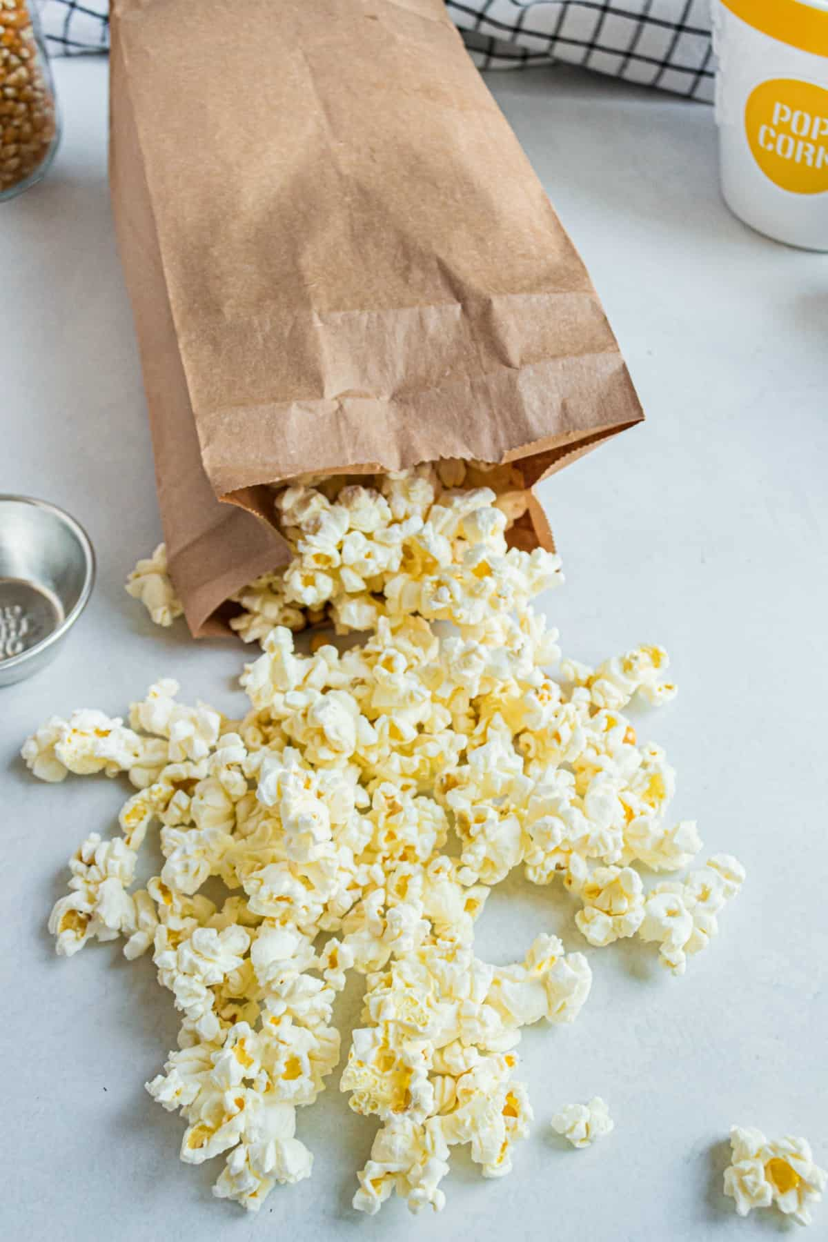 Cooked popcorn falling out of a brown paper bag.