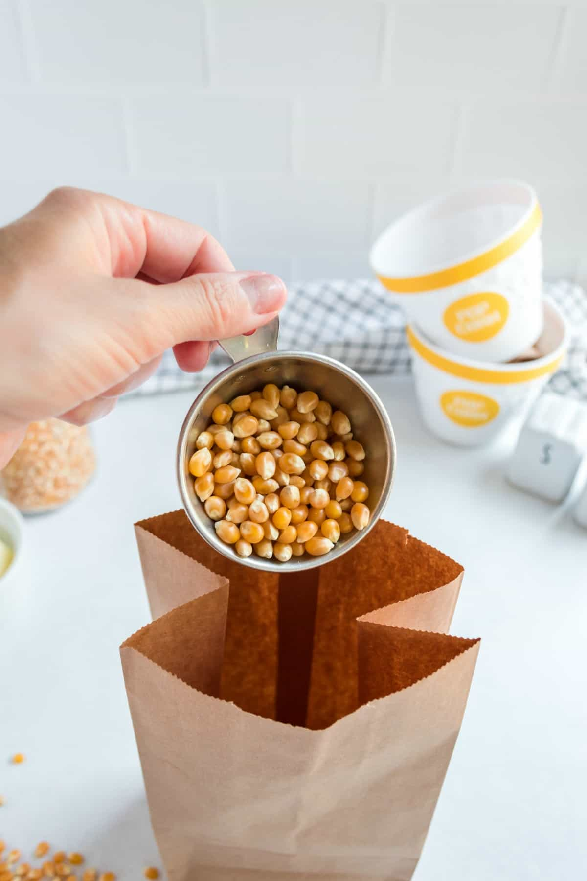 Popcorn kernels being scooped into a brown paper bag.