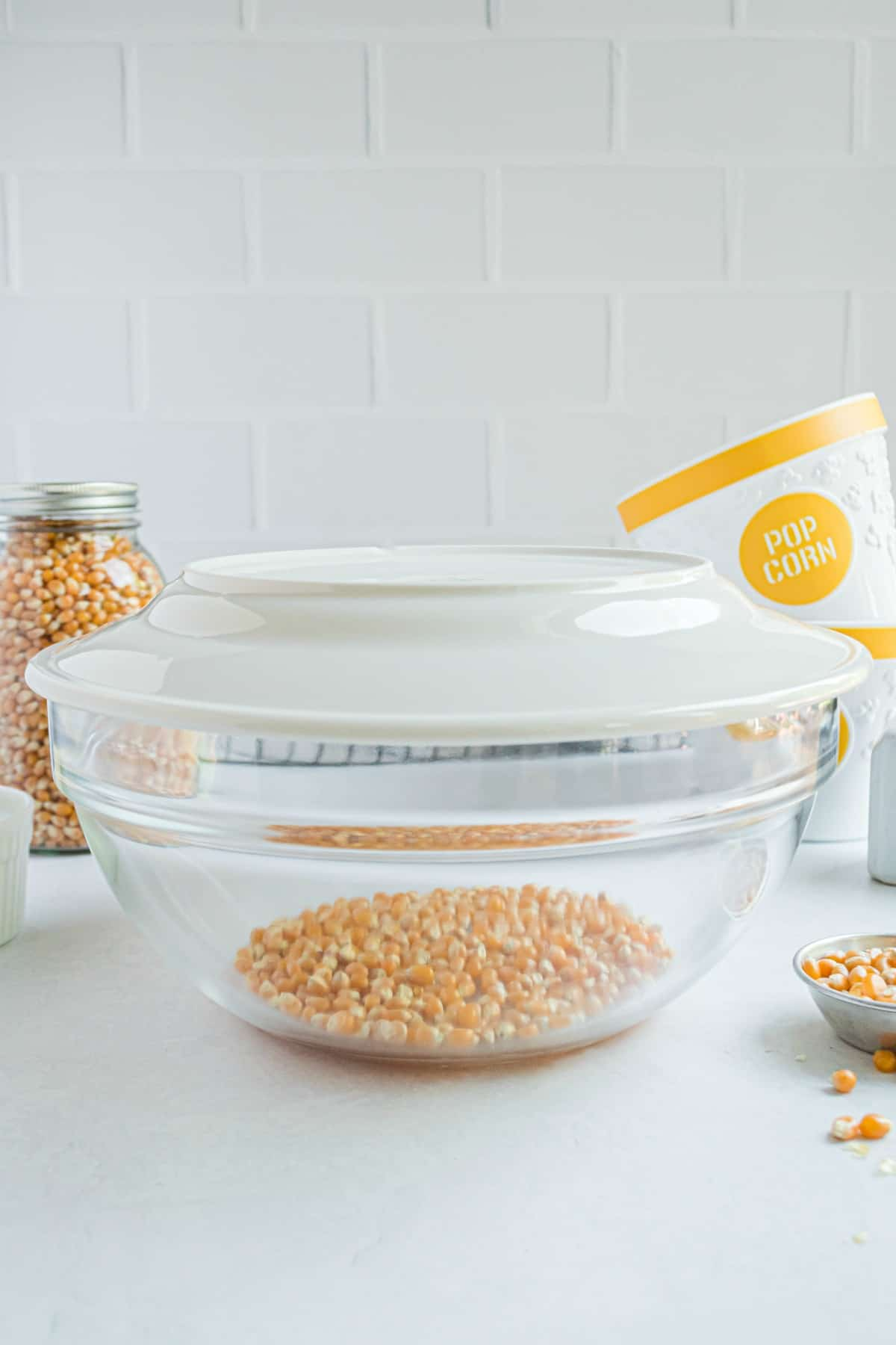 Glass bowl with white plate and popcorn kernels in bowl.