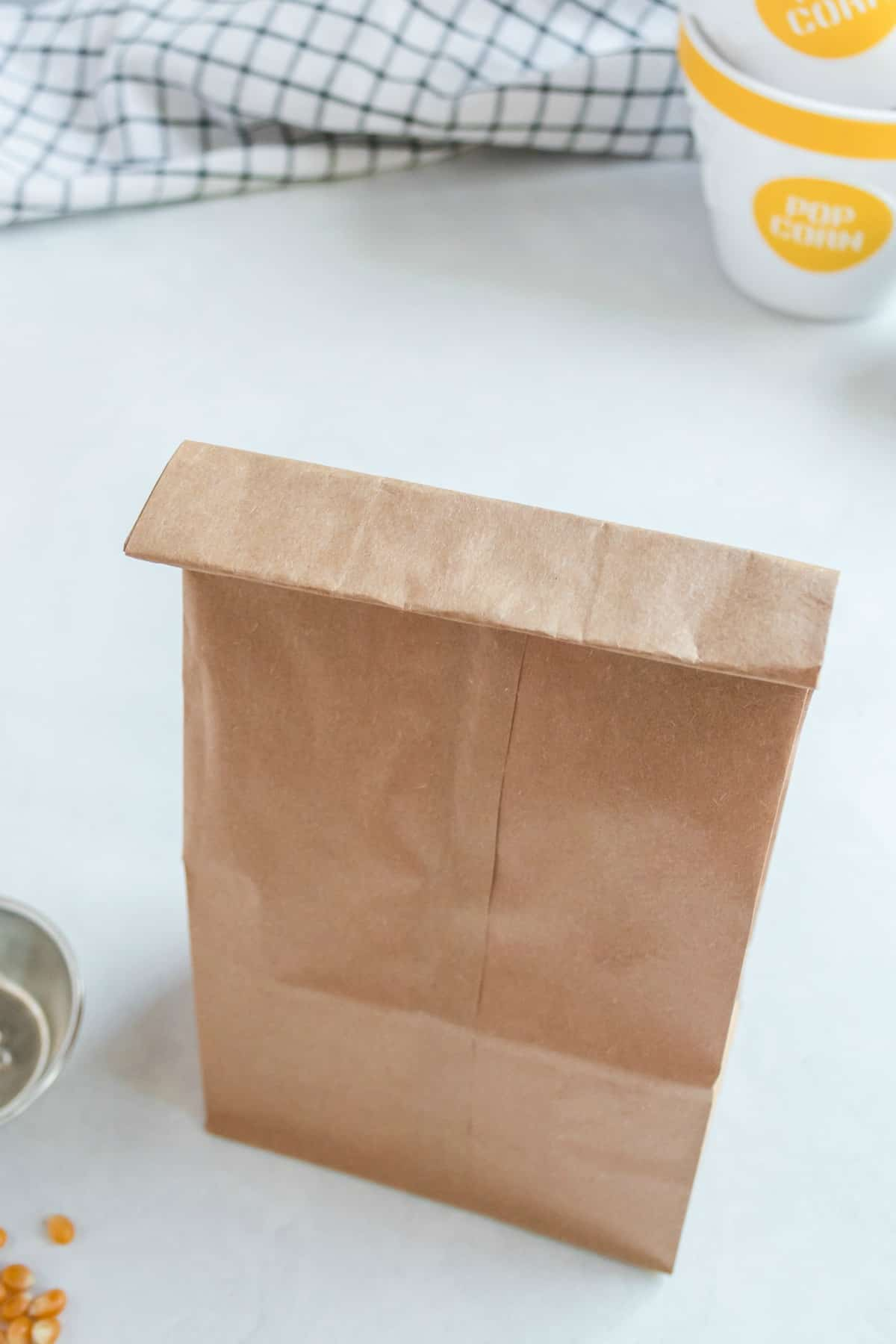 Brown paper bag folded over with popcorn inside.