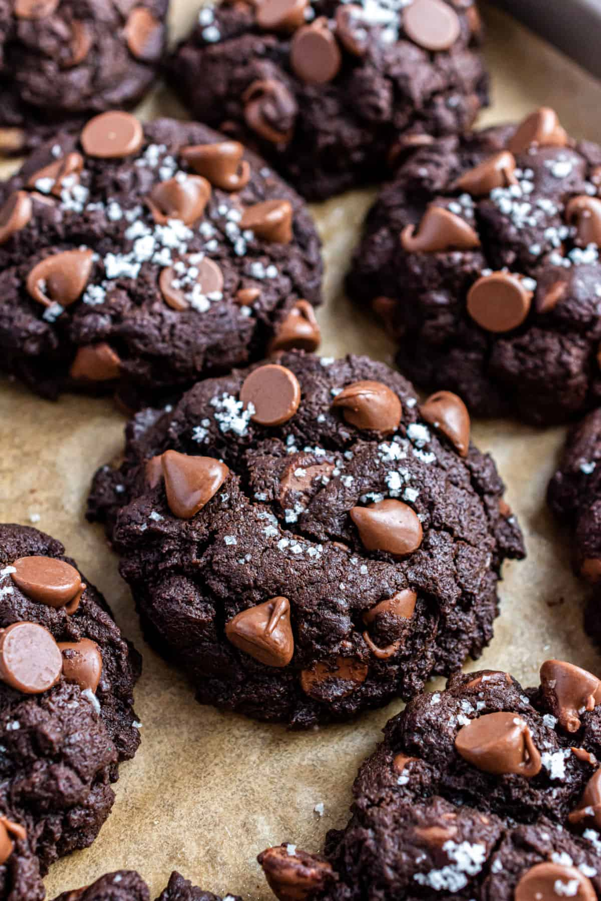 Chocolate cookies with chocolate chips and sea salt on parchment paper.