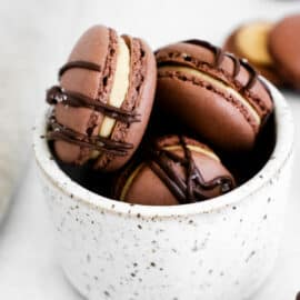 Chocolate macarons with peanut butter filling in a white marble cup.