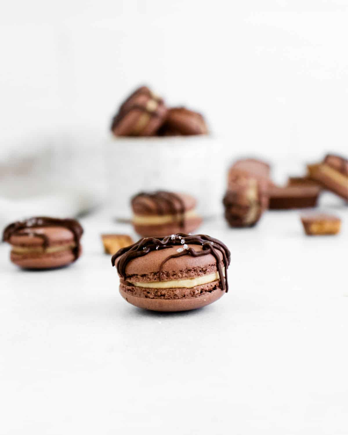 Chocolate macarons with peanut butter filling and chocolate drizzle.