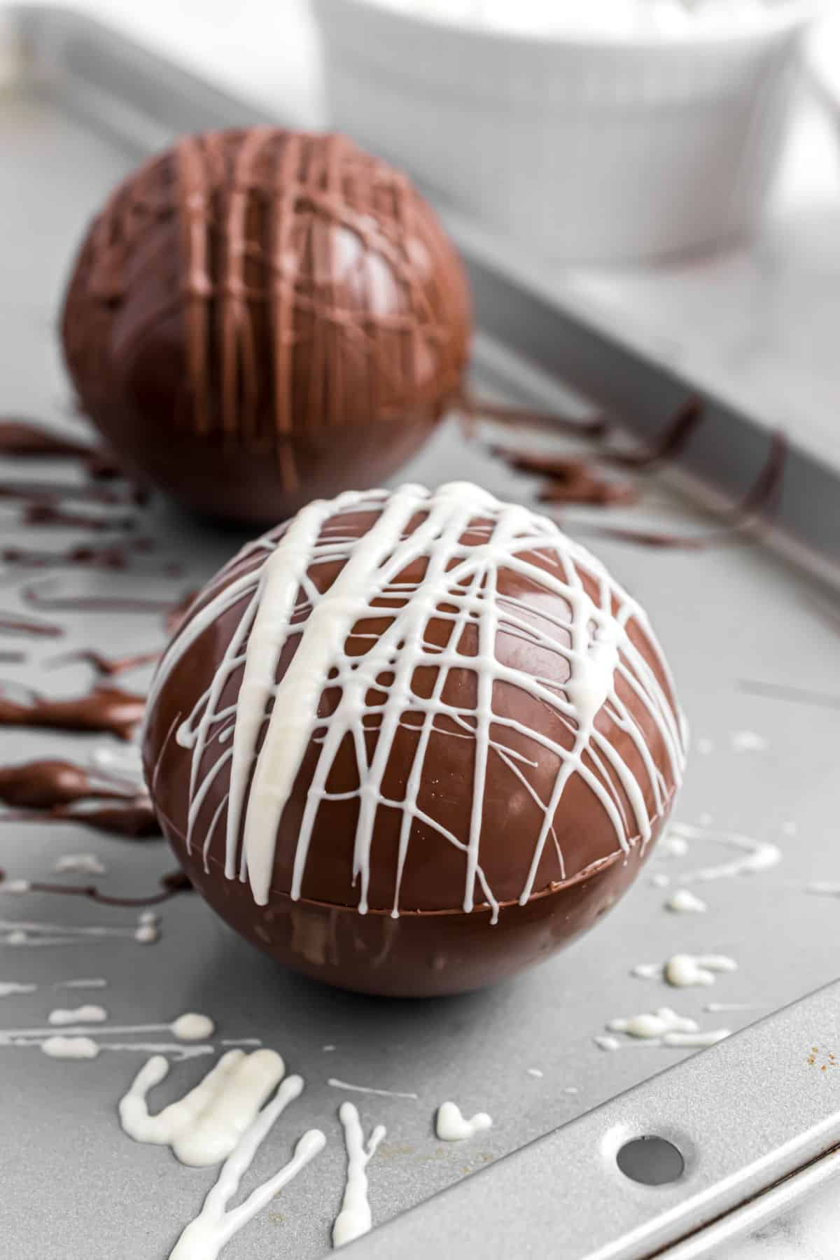 White chocolate drizzled on top of dark chocolate hot cocoa bombs.