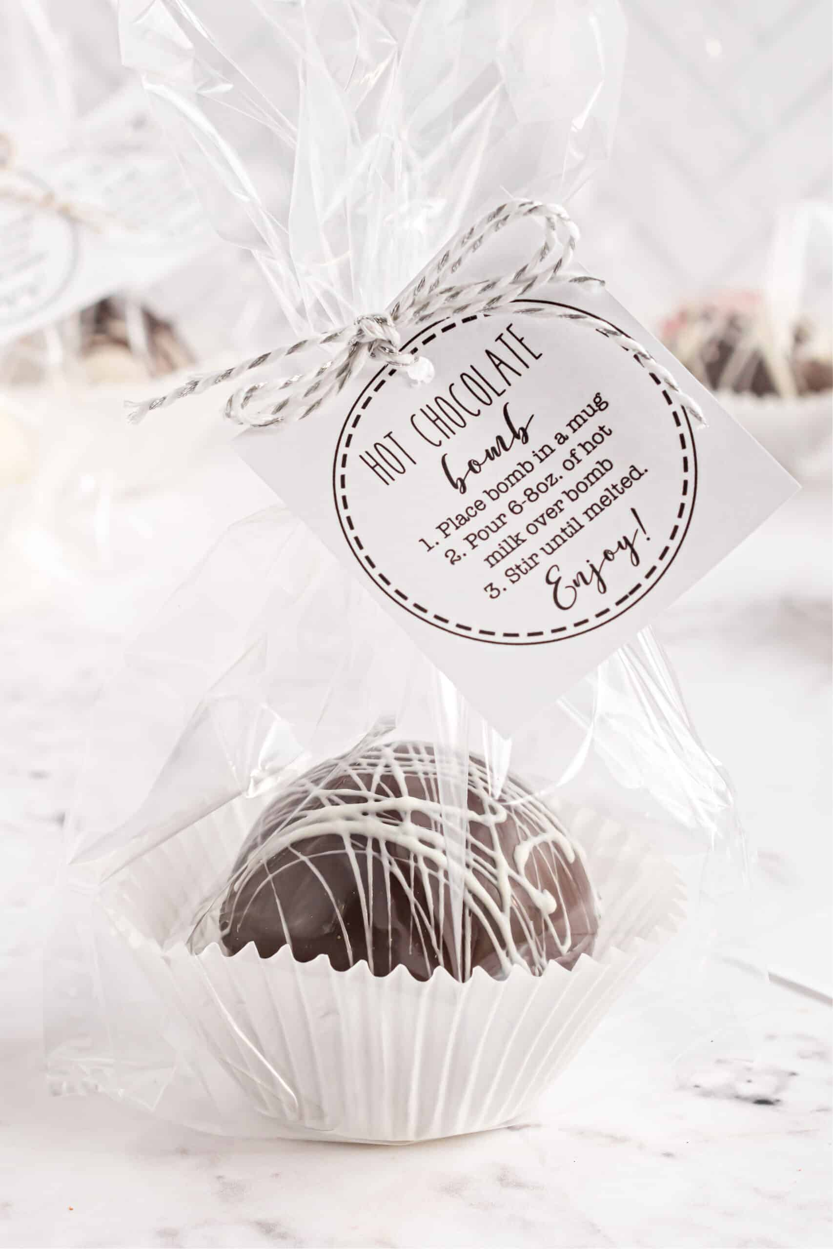 Hot chocolate bomb wrapped in clear cellophane with a tag attached.