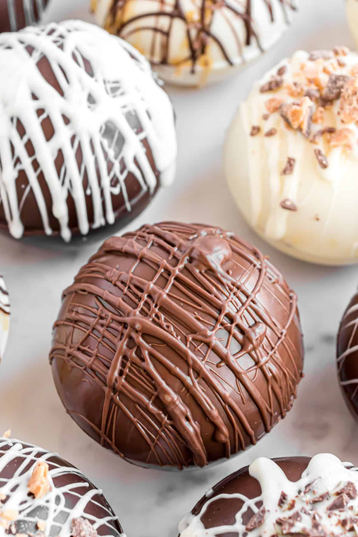 Hot chocolate cocoa bombs on a parchment paper baking sheet ready to use.
