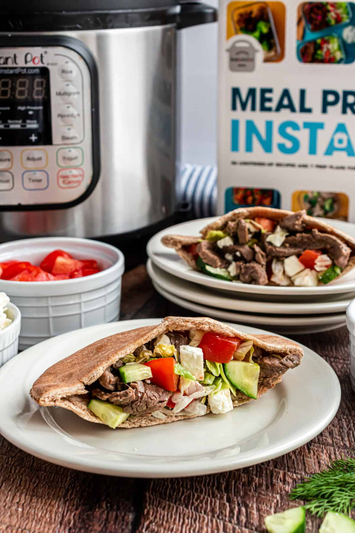 Beef gyros in a pita with vegetables and feta cheese.