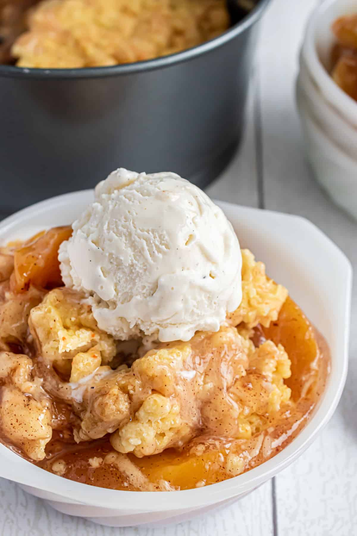 Peach cobbler served in a white bowl with vanilla ice cream on top.