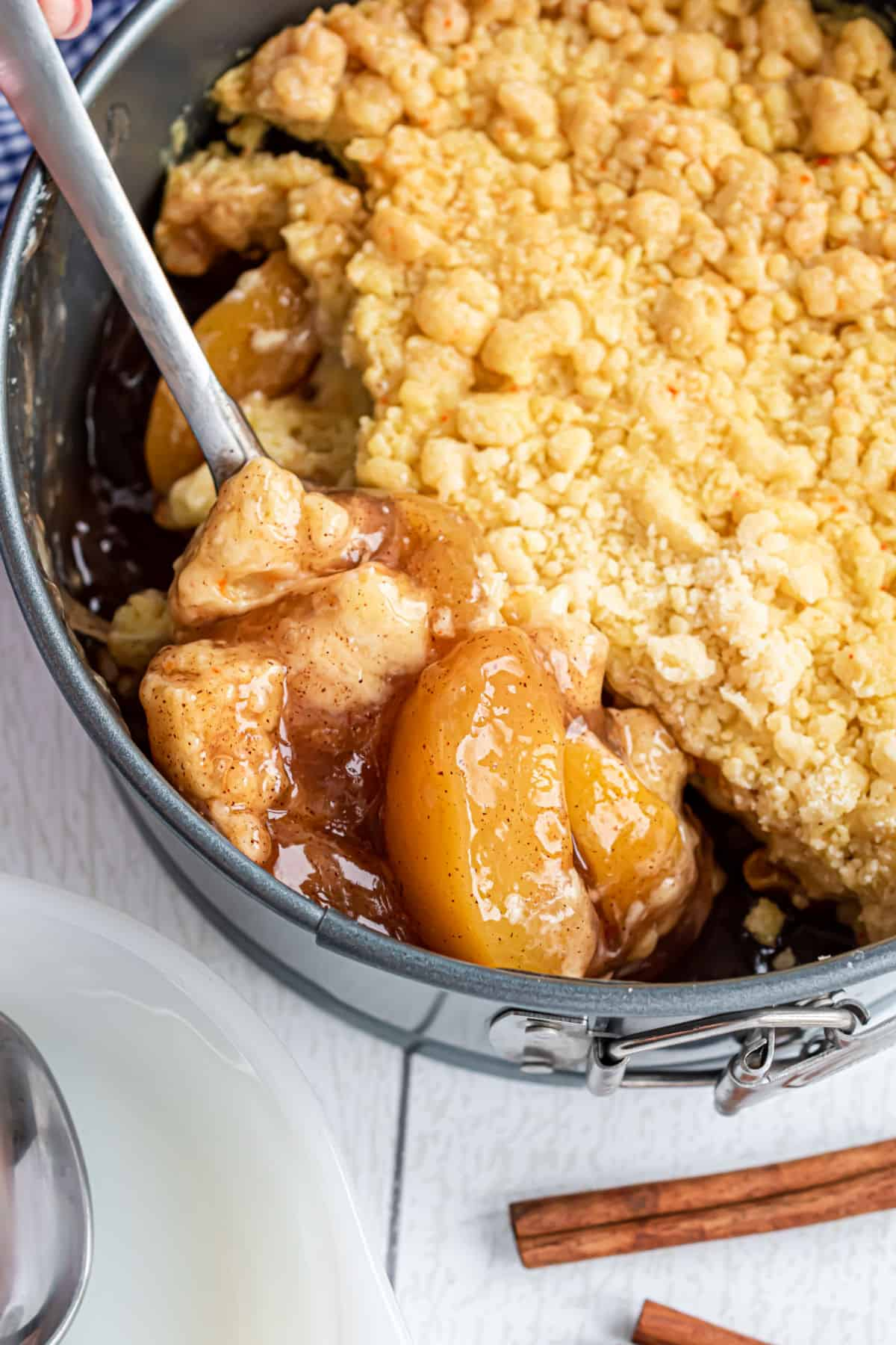 Scoop of peach cobbler being removed from springform pan.
