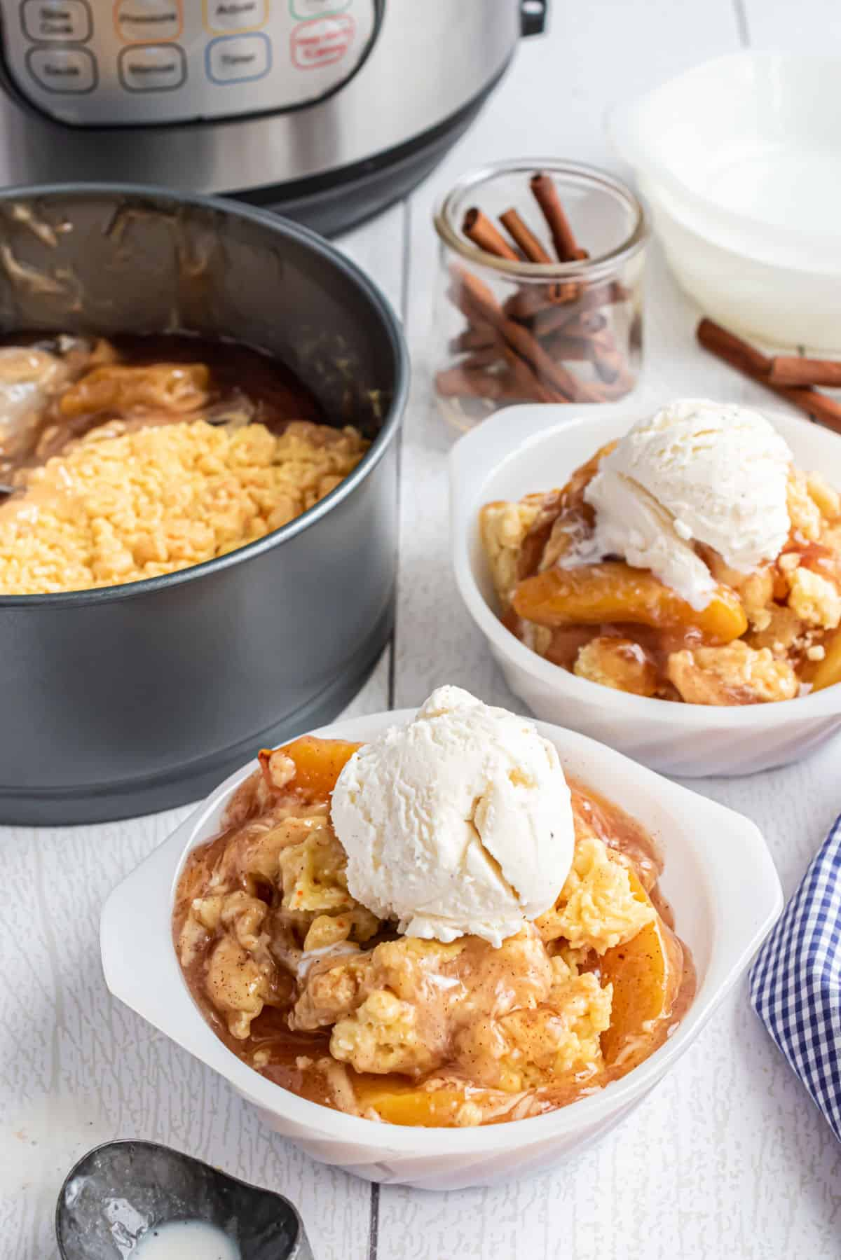 Peach cobbler made in the pressure cooker and served in a white bowl with vanilla ice cream.