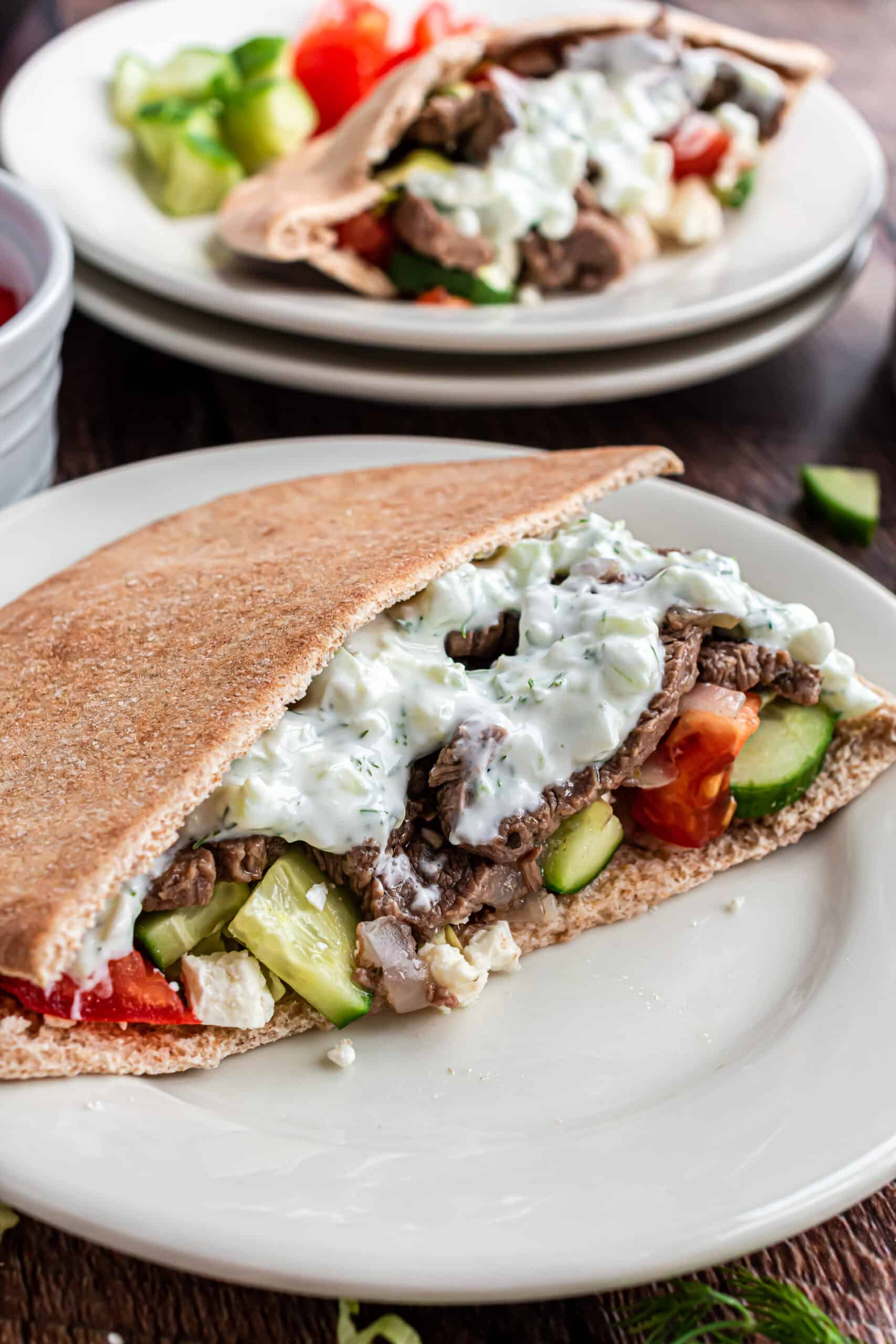 Dinner plate with whole wheat pita, beef gyros, and tzatziki sauce.