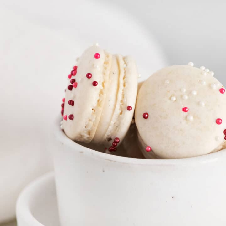 Vanilla bean macarons with pink sprinkles in a white bowl.