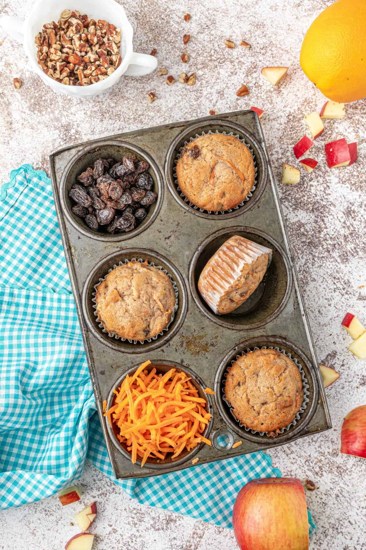 Morning glory muffins styled in a cupcake tin with shredded carrots and raisins.