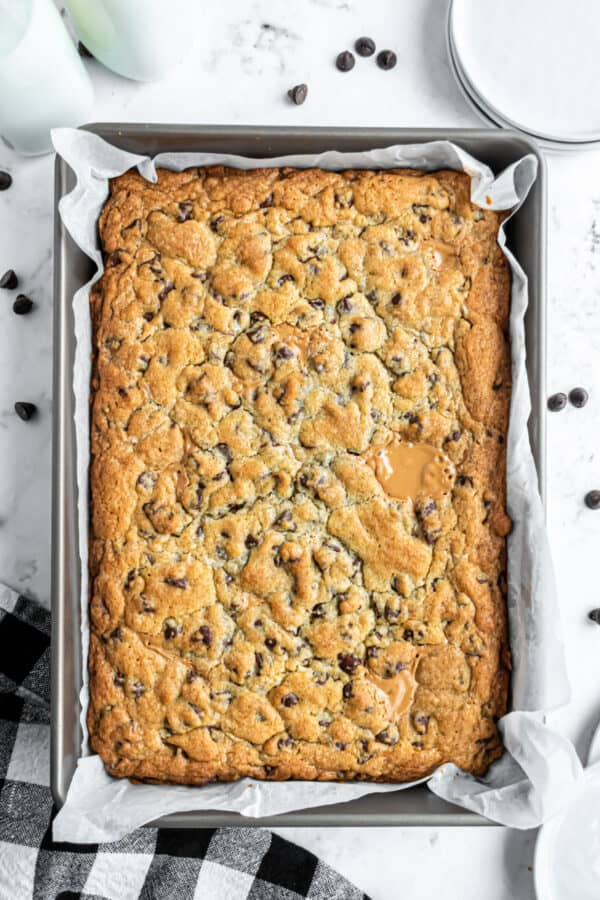 Baked peanut butter swirled chocolate chip cookie bars in a parchment paper lined 13x9 baking dish.