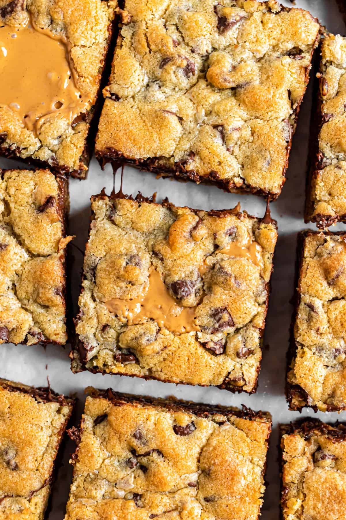 Chocolate chip peanut butter swirled cookie bars on a parchment paper lined baking sheet.