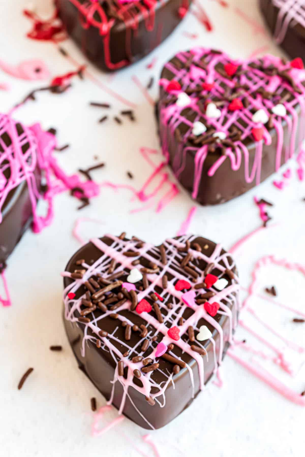 Heart shaped hot chocolate bombs with pink and red chocolate drizzle.