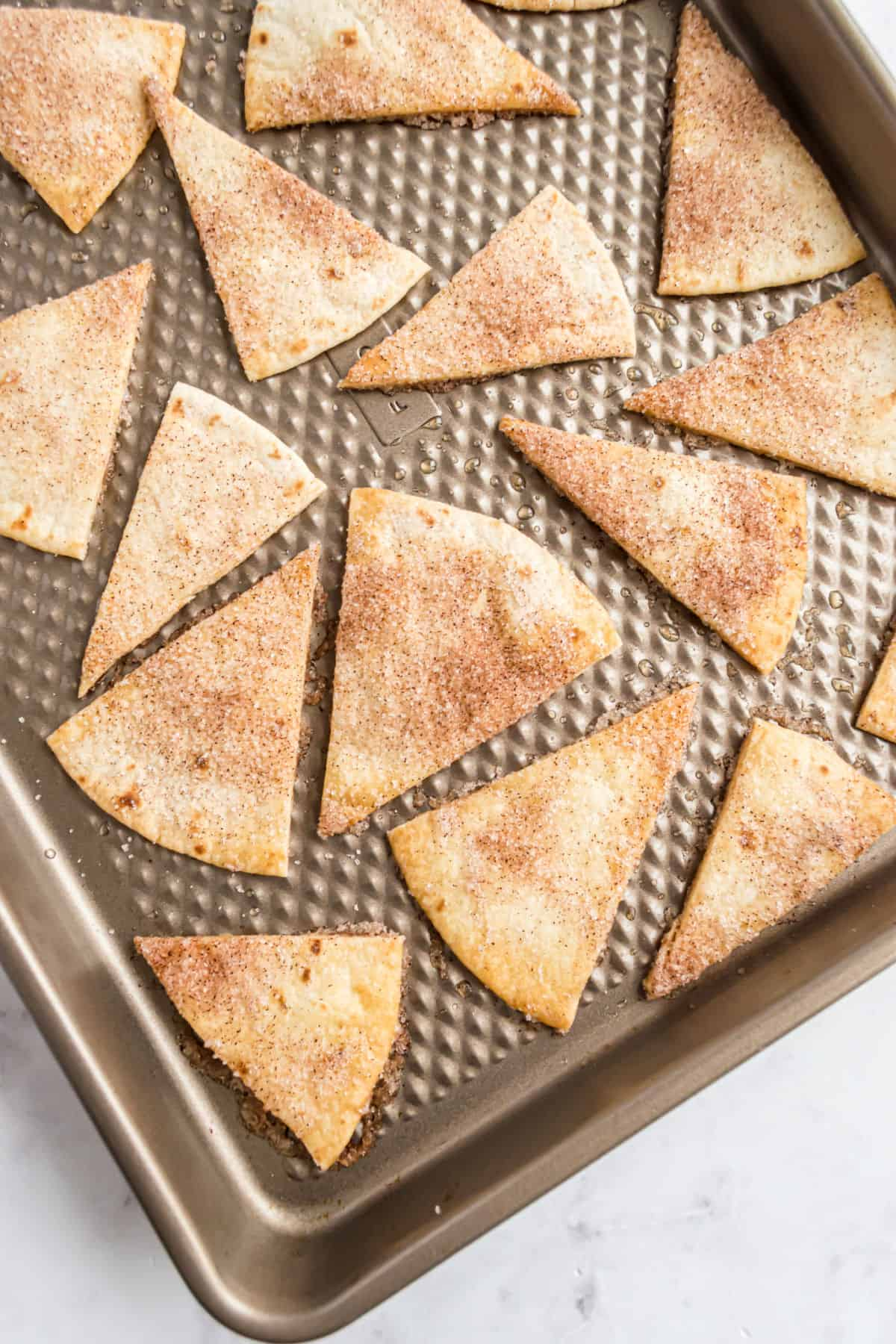 Cinnamon tortilla chips on a baking sheet.