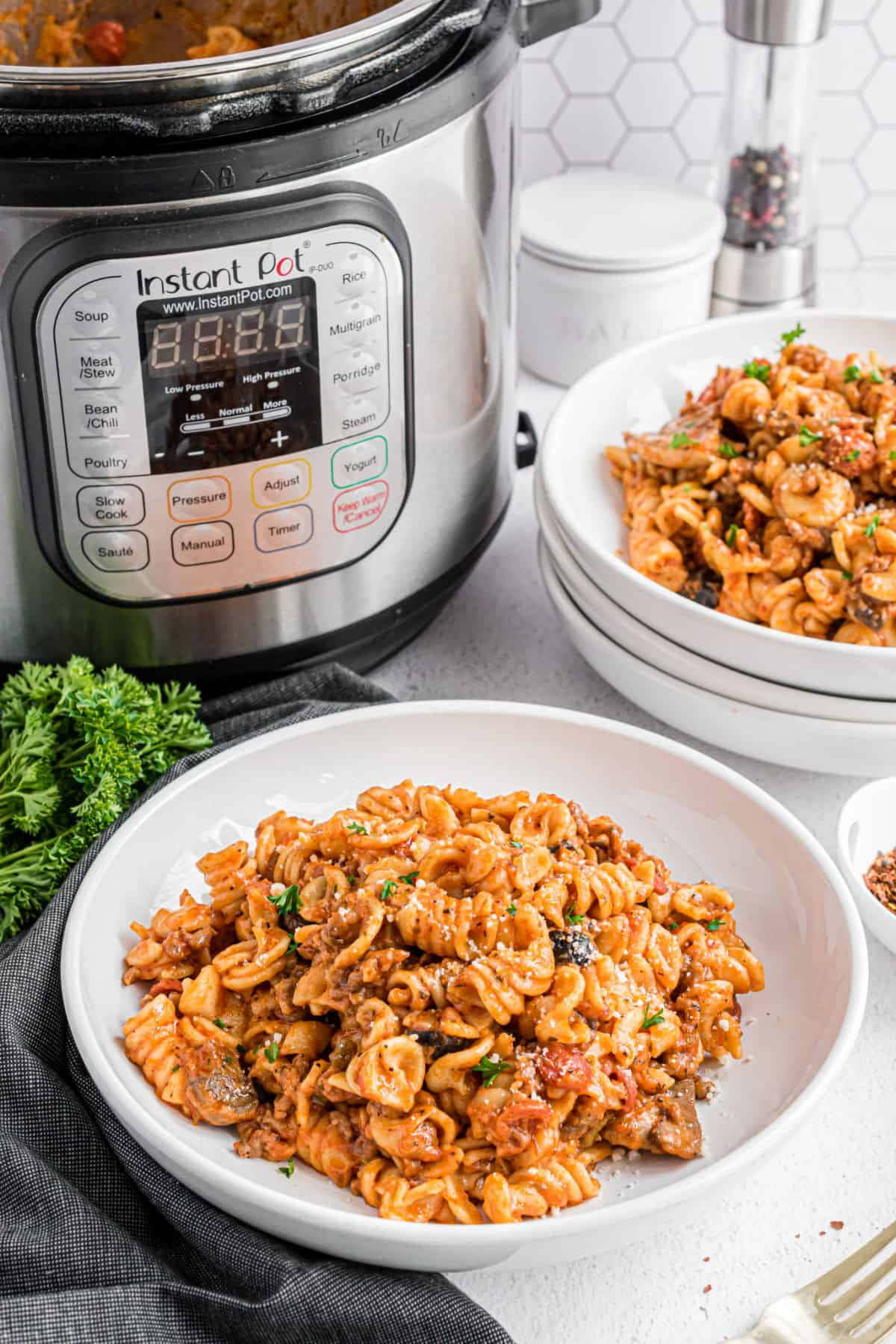 Pizza pasta in a bowl with instant pot in background.
