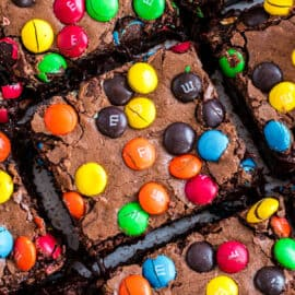 Squares of M&M brownies on a piece of parchment paper.