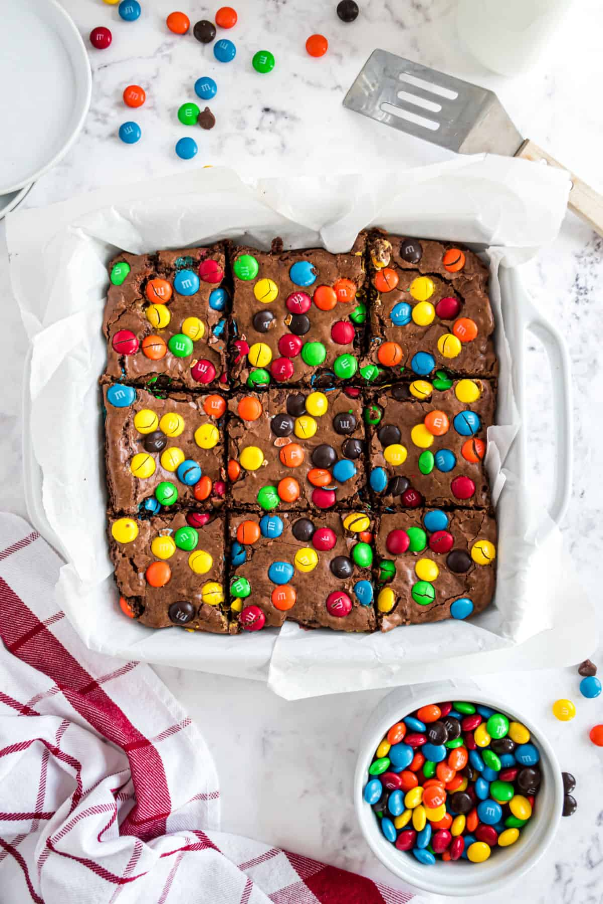 M&Ms brownies in a square baking dish with parchment paper cut into 9 squares.